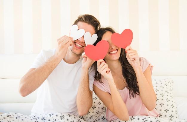 Gelukkige paar poseren met papier hart Gratis Foto