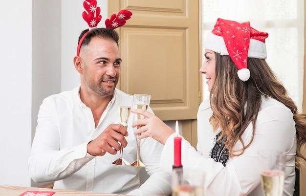 Gelukkige paar rinkelende champagneglazen op feestelijke tafel Gratis Foto