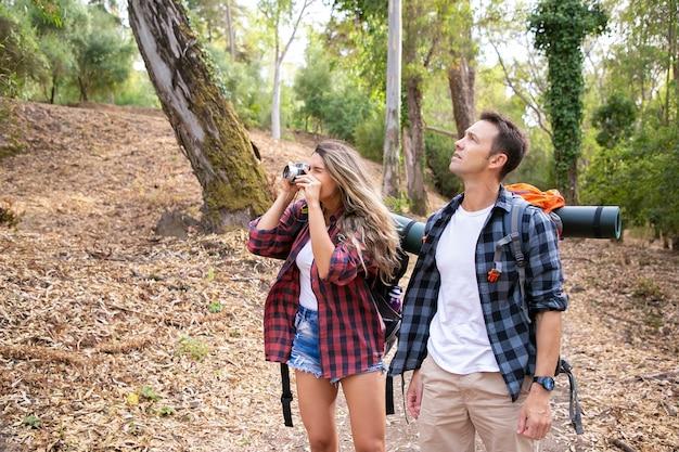 Gelukkige paar samen reizen, foto's nemen en wandelen in het bos. twee kaukasische backpackers die door bos lopen. vrouw natuur fotograferen op camera. toerisme, avontuur en zomervakantie concept Gratis Foto