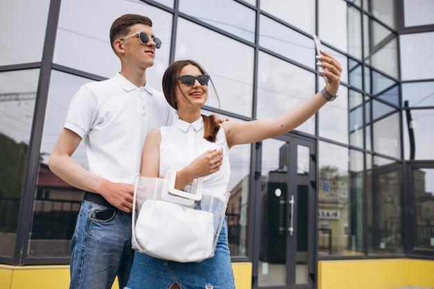 Gelukkige paar samen uit in de stad met behulp van de telefoon Gratis Foto