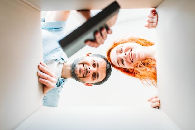Gelukkige paar, uitzicht vanuit de kartonnen doos, verhuizen naar een nieuw huis. man en vrouw kartonnen dozen, housewarming uitpakken Premium Foto