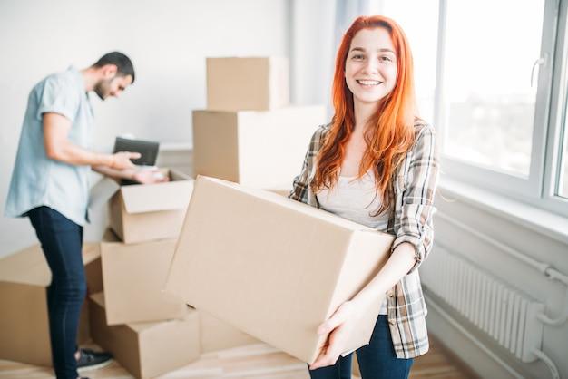 Gelukkige paar verhuizen naar een nieuw huis. man en vrouw kartonnen dozen, housewarming uitpakken Premium Foto
