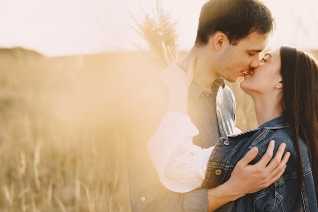 Gelukkige paar verliefd in tarweveld bij zonsondergang Gratis Foto