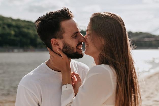 Gelukkige paar verliefd knuffelen en zoenen samen op het strand in warme zonnige dag Gratis Foto
