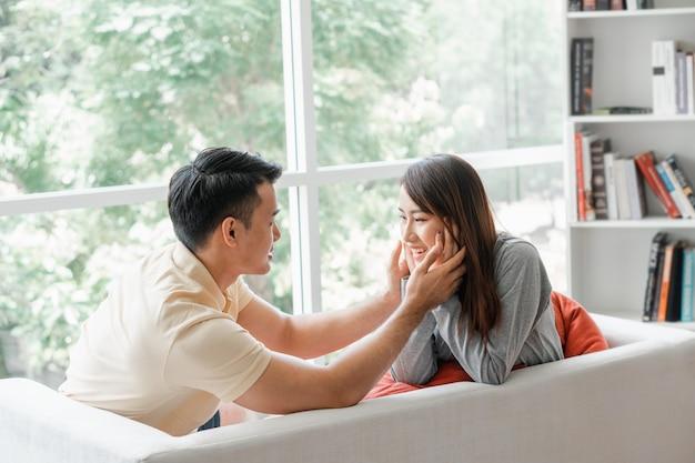 Gelukkige paar zittend op de bank en een man zijn plaagt zijn vriendin met liefde in de woonkamer en glimlach. Premium Foto