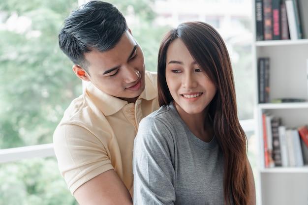 Gelukkige paar zittend op de bank en een man zijn plaagt zijn vriendin met liefde in de woonkamer en ontspan. Premium Foto