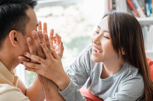 Gelukkige paar zittend op de bank en een man zijn plaagt zijn vriendin met liefde in de woonkamer Premium Foto