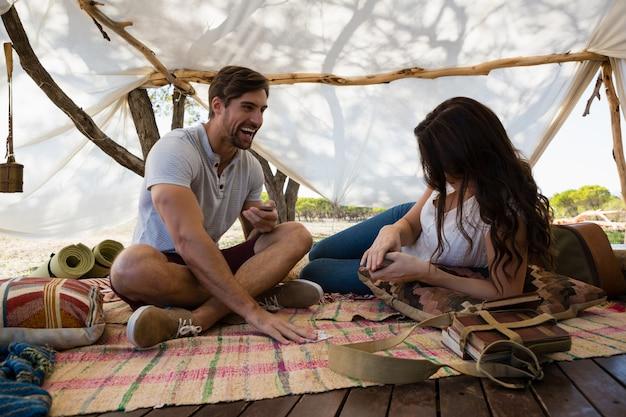 Gelukkige paarspeelkaarten in tent Gratis Foto