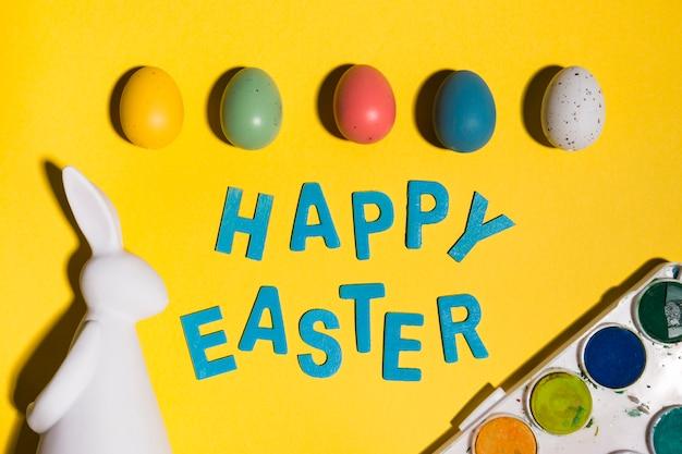 Gelukkige pasen-inschrijving met eieren en konijn op lijst Gratis Foto