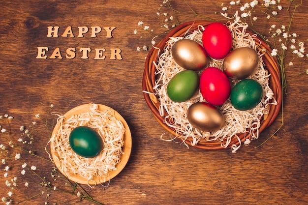 Gelukkige pasen-woorden dichtbij heldere eieren op schotels met klatergoud dichtbij installaties Gratis Foto