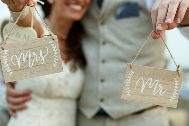 Gelukkige pasgetrouwden houden houten planken met letters 'mevrouw' en 'meneer' Gratis Foto