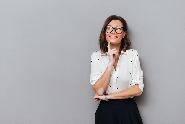 Gelukkige peinzende vrouw in oogglazen en bedrijfskleding die vinger dichtbij de kin houden en weg op grijs kijken Gratis Foto