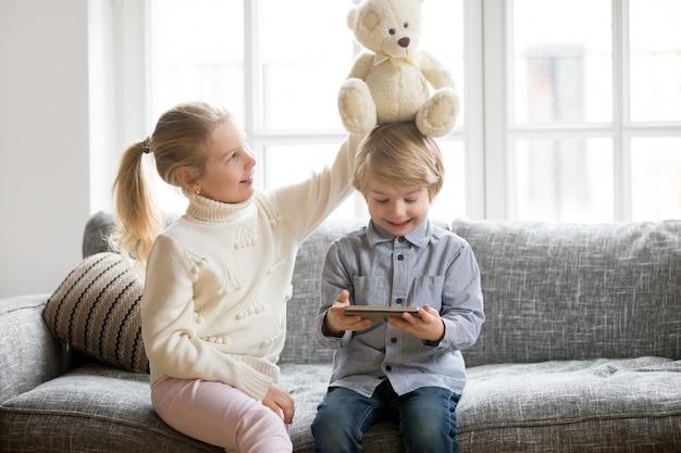 Gelukkige peuterjongen die tablet gebruiken terwijl zuster het spelen met stuk speelgoed Gratis Foto