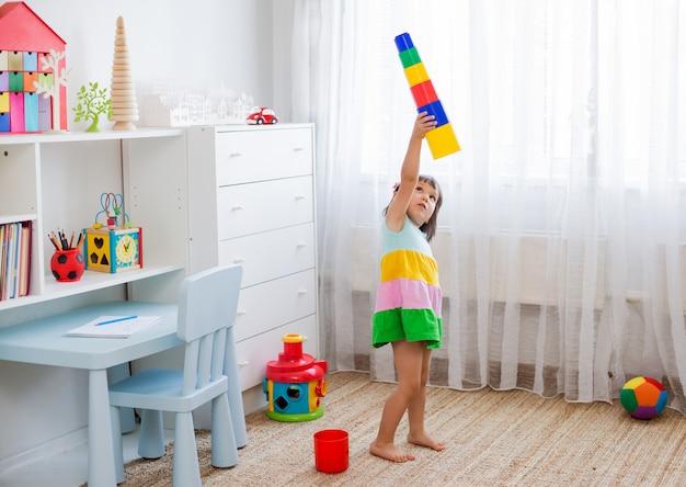 Gelukkige peuterleeftijdskinderen spelen met kleurrijke plastic stuk speelgoed blokken. Premium Foto