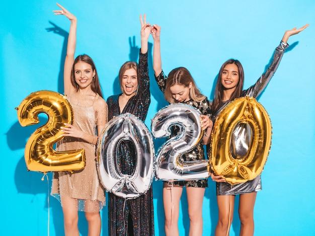 Gelukkige prachtige meisjes in stijlvolle sexy feestjurken met gouden en zilveren 2020-ballonnen Gratis Foto