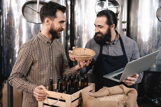 Gelukkige professionele brouwers die de mout inspecteren. Premium Foto