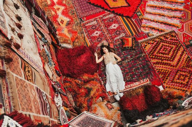 Gelukkige reisvrouw met verbazende kleurrijke tapijten in lokale tapijtwinkel, goreme. Premium Foto