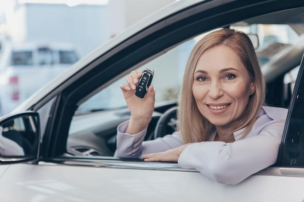 Gelukkige rijpe vrouwenzitting in haar nieuwe automobiele sleutel van de holdingsauto Premium Foto