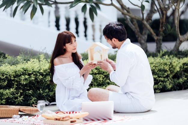 Gelukkige romantische parenminnaar die en wijn spreken drinken terwijl thuis het hebben van een picknick Premium Foto