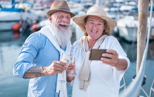 Gelukkige senior paar doen selfie, juichen met champagne op een zeilboot tijdens jubileumvakantie Premium Foto