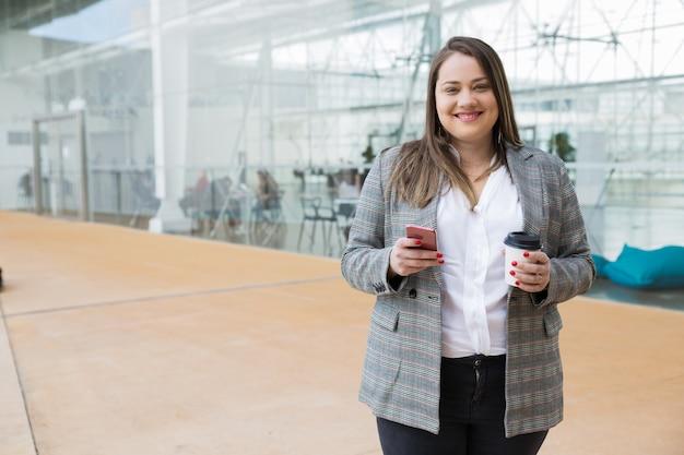 Gelukkige smartphone van de bedrijfsvrouwenholding en drank in openlucht Gratis Foto