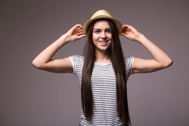 Gelukkige speelse vrouw die fedora van het de zomerstro draagt die over schouder aan de kant kijkt Gratis Foto