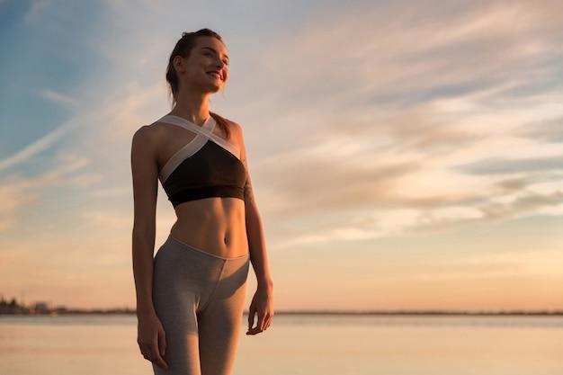 Gelukkige sportenvrouw bij het strand dat opzij kijkt. Gratis Foto