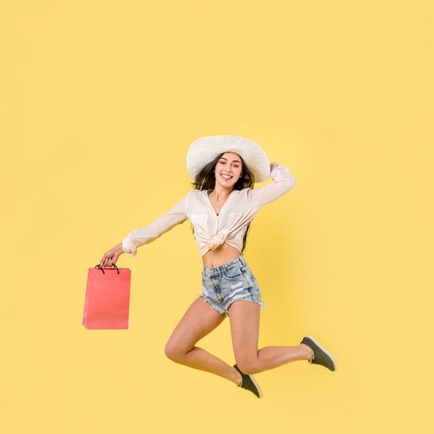 Gelukkige springende vrouw met rode papieren zak Gratis Foto