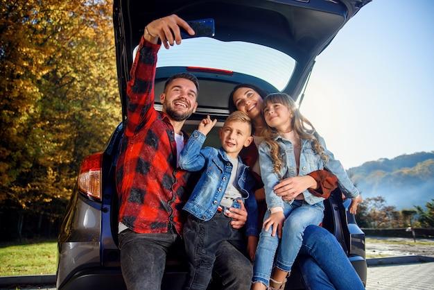 Gelukkige stijlvolle ouders met hun schattige lieve kinderen maken grappige selfie op smartphone terwijl ze in de kofferbak zitten. gelukkig modern familieconcept. Premium Foto