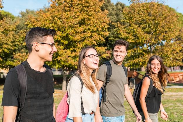 Gelukkige studenten bij park dat en pret glimlacht heeft Premium Foto