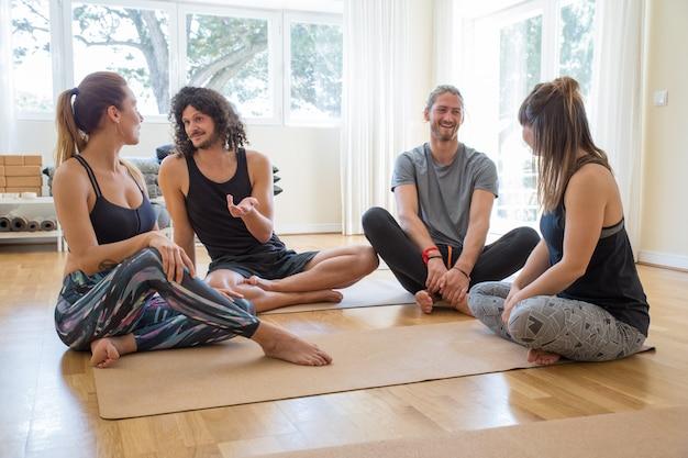 Gelukkige studenten die na yogaklasse babbelen Gratis Foto