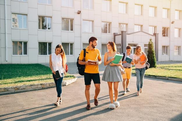 Gelukkige studenten met boeken in handen die samen op campus lopen Gratis Foto