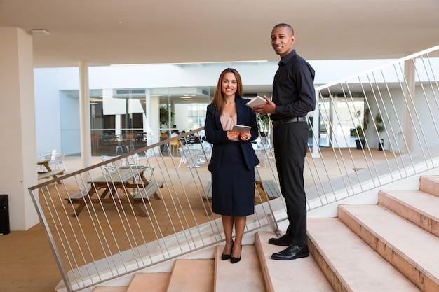 Gelukkige succesvolle commerciële teamleden die in bureau stellen Gratis Foto