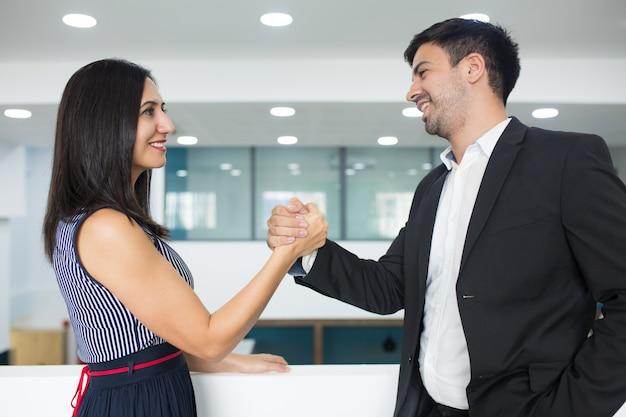 Gelukkige succesvolle partners die sterke handdruk maken Gratis Foto