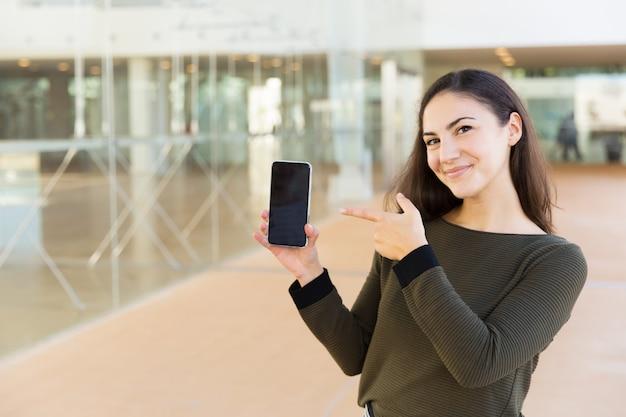 Gelukkige tevreden cellphonegebruiker die op het lege scherm richt Gratis Foto