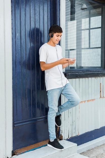 Gelukkige tiener die zich bij gesloten blauwe deur bevindt die mobiele telefoon met hoofdtelefoon op zijn hoofd met behulp van Gratis Foto