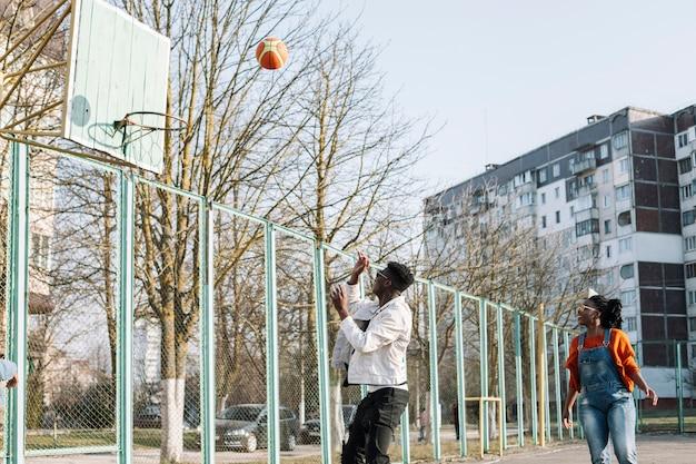 Gelukkige tieners die basketbal in openlucht spelen Gratis Foto