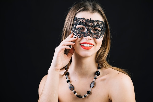 Gelukkige topless vrouw die het masker van maskeradecarnaval over zwarte achtergrond draagt Gratis Foto