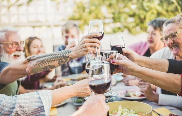 Gelukkige trendy familie die met rode wijn bij barbecuediner toejuichen openlucht Premium Foto