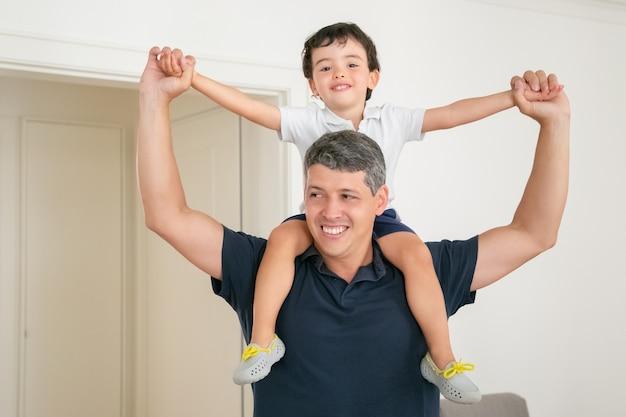 Gelukkige vader die zijn zoon op schouders houdt en handen spreidt. Gratis Foto