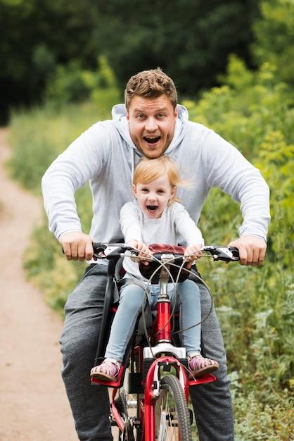 Gelukkige vader en dochter op fiets Gratis Foto