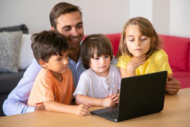 Gelukkige vader en kinderen samen film kijken via laptop. kaukasische vader aan tafel zitten en schattige kinderen omarmen. jongens en meisje die het scherm bekijken. vaderschap en digitale technologie concept Gratis Foto