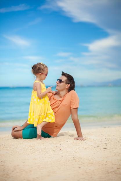 Gelukkige vader en zijn schattige kleine dochter hebben plezier op het strand Premium Foto