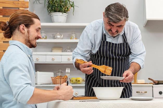 Gelukkige vader en zoon die voorbereidingen treffen te eten Gratis Foto