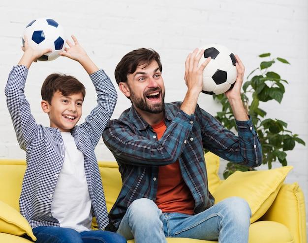 Gelukkige vader en zoon houden van voetballen Gratis Foto