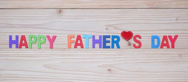 Gelukkige vaderdagtekst met rode hartvorm op houten achtergrond. Premium Foto