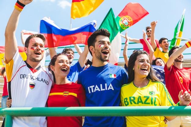 Gelukkige ventilatorsverdedigers van verschillende landen samen bij stadion Premium Foto