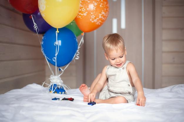Gelukkige verjaardag baby spelen met ballonnen Premium Foto