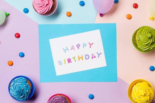 Gelukkige verjaardag bericht op wit papier omringd met edelstenen en muffins op gekleurde achtergrond Gratis Foto