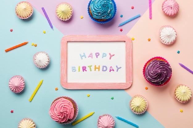 Gelukkige verjaardag geschreven op houten frame omringd met muffins; aalaw; hagelslag en kaarsen op gekleurde achtergrond Gratis Foto